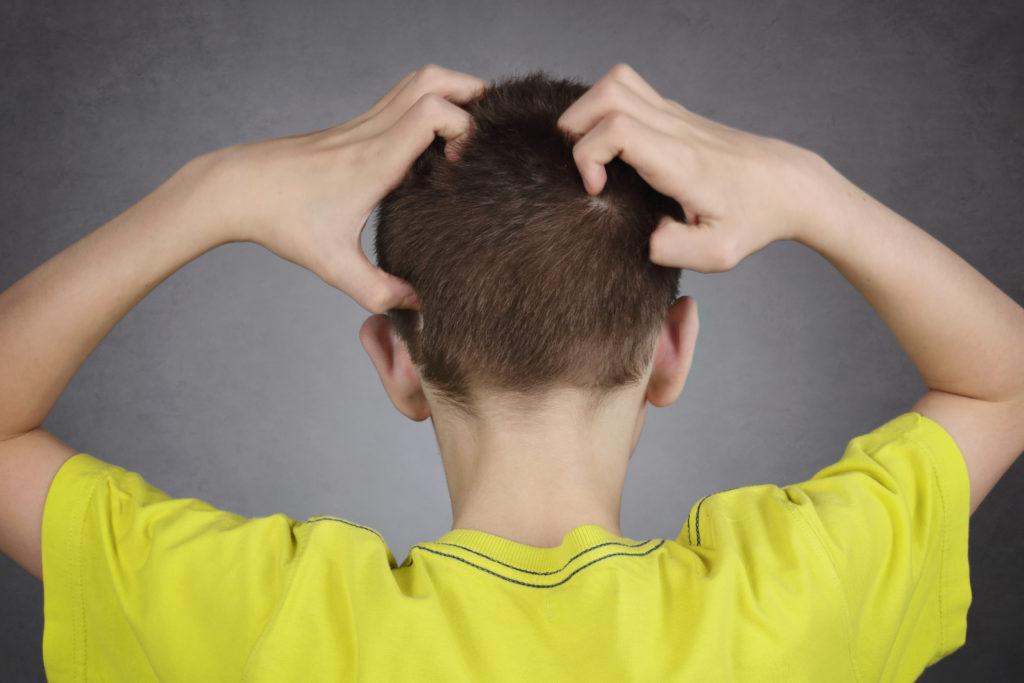 Niño con piojos en la cabeza