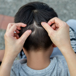 Mamá buscando piojos en el cabello